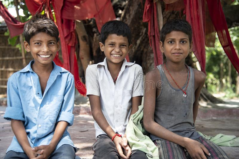 Three poor Indian boys posing for a portrait in a village in Bihar, India. The photo was taken in Muzaffarpur, India where the three friends were sitting royalty free stock photo