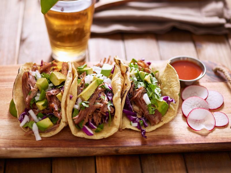 Three  pork carnitas street tacos in yellow corn tortilla with avocado, onion, cilantro and cabbage. On wooden table stock images