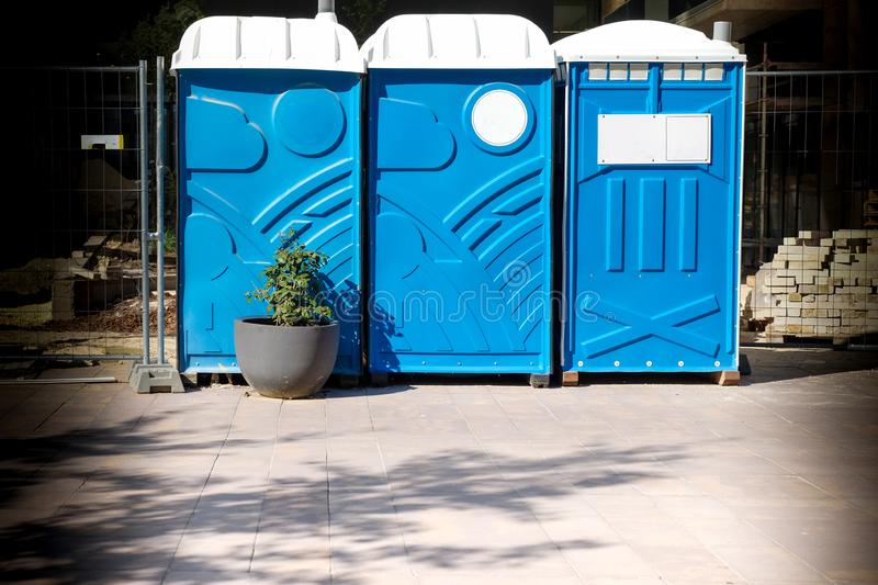 Three portable blue WC toilet cabins at construction site royalty free stock photos