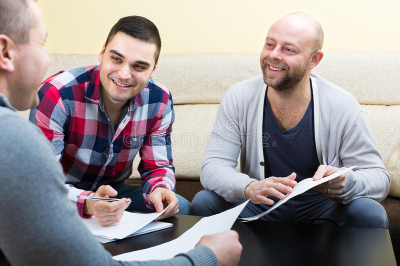 Three positive males with documents. At agency royalty free stock photography