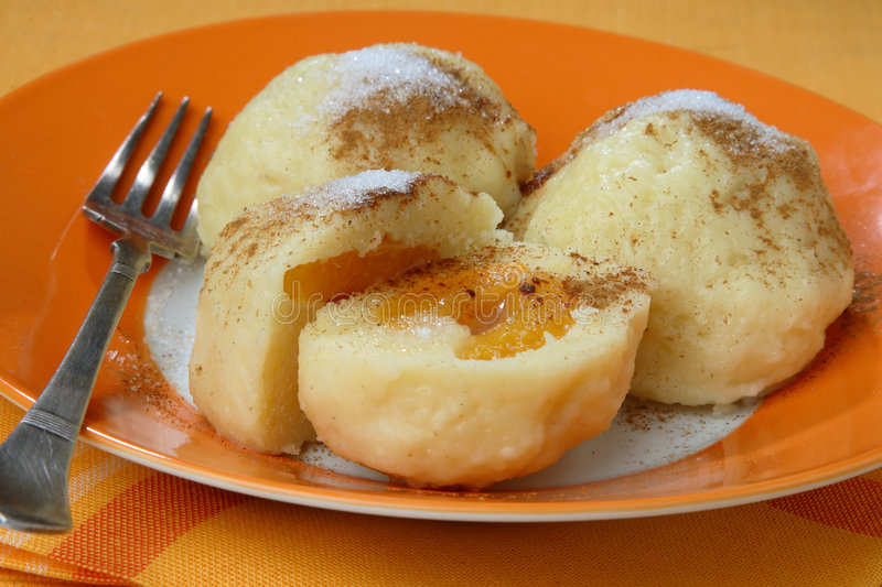 Three potato dumplings. Filled with apricots one cut in half royalty free stock photo