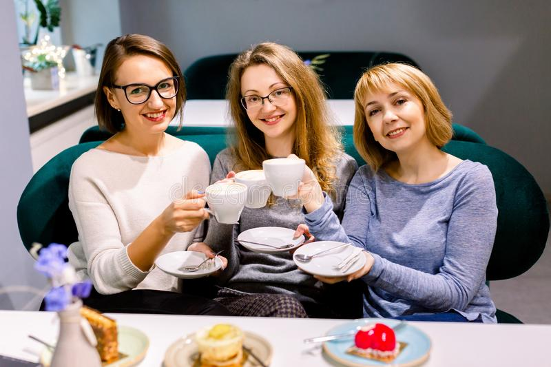Three pretty Caucasian girl friends spend time together drinking coffee in the cafe, having fun and eating cakes and. Dessert stock photo