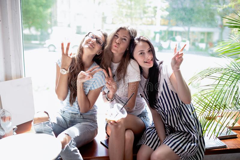 Three pretty slim girls with long dark hair,wearing casual style,sit on the windowsill in a modern coffee shop.  stock photography