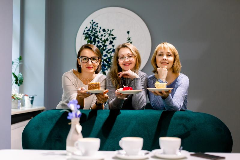 Three pretty women friends holding plates with colorful cakes looking at camera in cafe indoors. Picture presenting royalty free stock image