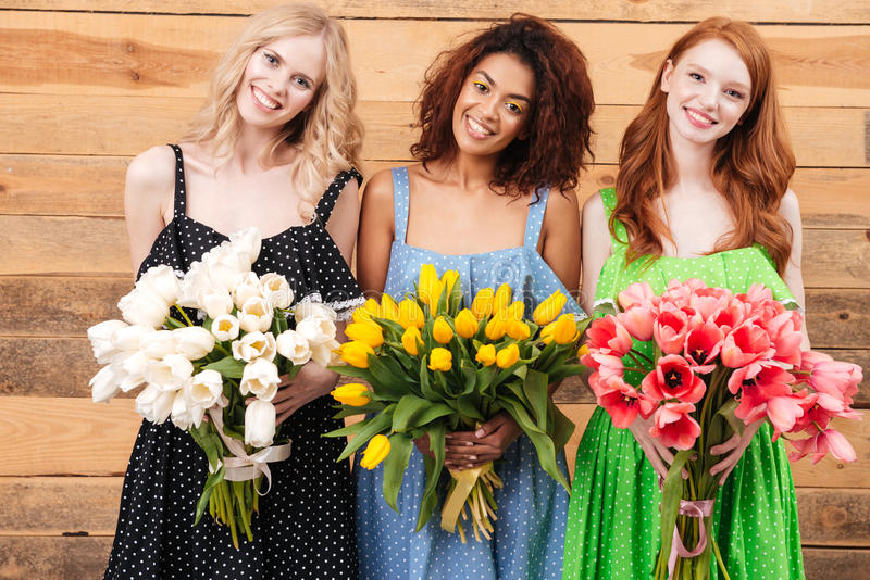 Three pretty women holding bouquets of flowers. Three pretty women in dresses posing near the wooden wall and holding bouquets of flowers while looking at the royalty free stock photo