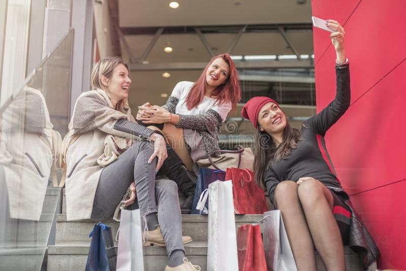 Three pretty young girls taking selfie in shopping mall stock images