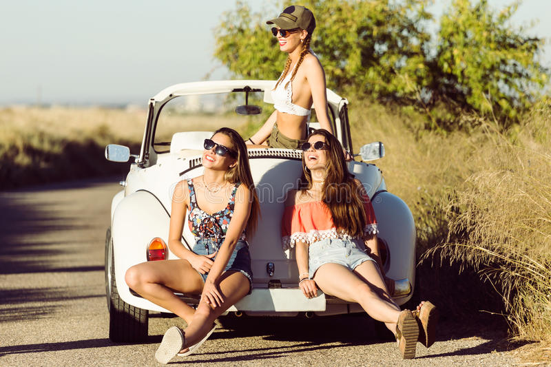 Three pretty young women driving on road trip on beautiful summe stock image