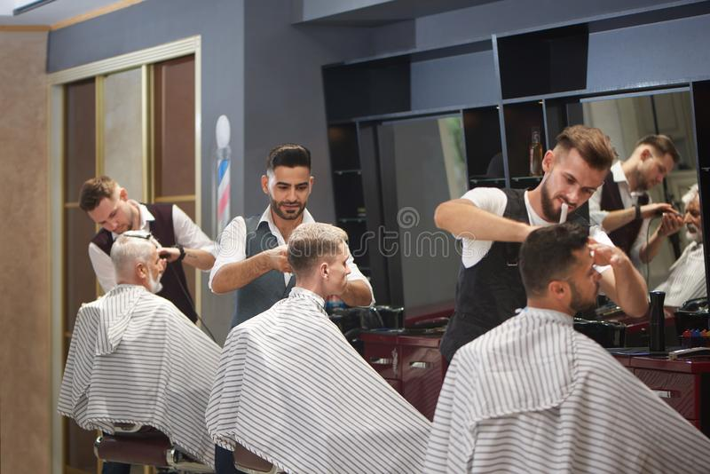 Three professional barbers trimming, cutting and styling male clients` hair. royalty free stock photography