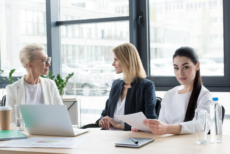 three professional different age businesswomen at meeting stock photo