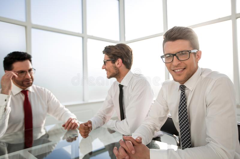 Three professional employees sitting at the office table royalty free stock image