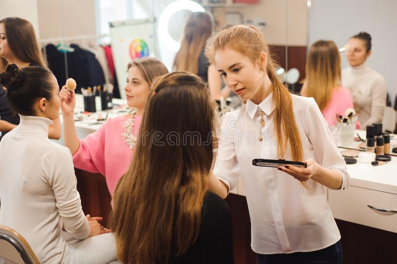 Three professional make-up artists work with beautiful women royalty free stock photos