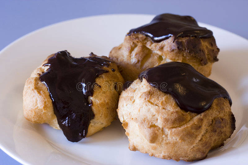 Three Profiteroles on a plate royalty free stock image