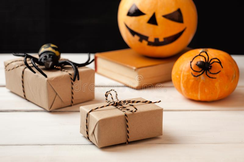 Three pumpkin with painted faces, gift boxes and decorative spiders on a wooden table on a background of black boards. Background. For Halloween royalty free stock photos