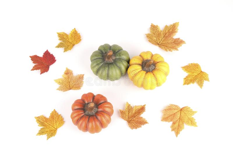 Three pumpkins made of clay between colorful leaves royalty free stock photos