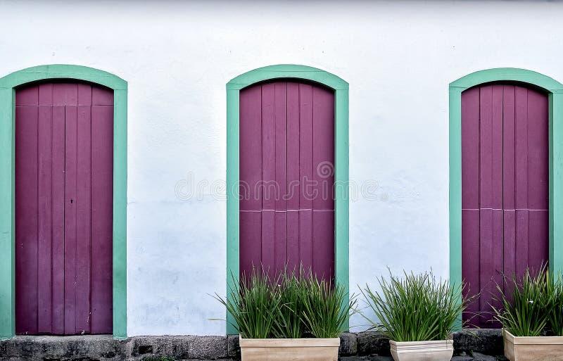 Three purple doors down street royalty free stock image