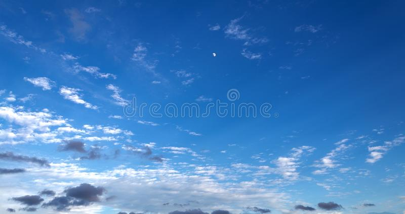 Three quarter moon rising as the sun sets on a dark blue sky. With wispy cumulus clouds royalty free stock image