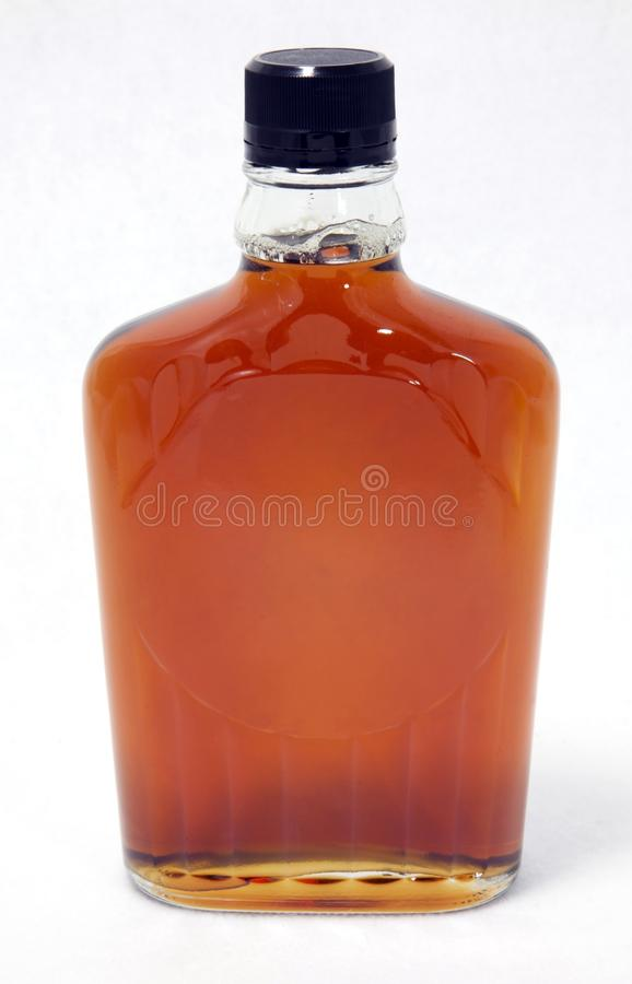 Bottle of Maple Syrup. Three-quarter view of isolated bottle of maple syrup royalty free stock image