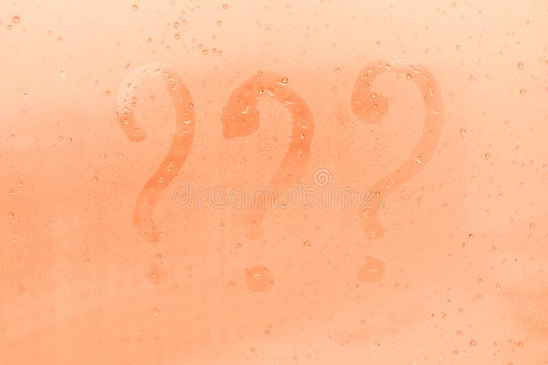 The three question marks picture or figure on the orange or pink evening or morning window glass. With drops royalty free stock photo