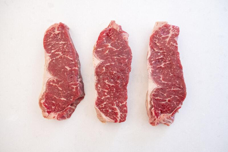 Three Raw Beef Strip Loins Steak Arranged Side by Side stock photo
