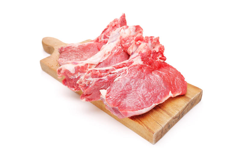 Three raw beefsteaks on a wooden cutting board royalty free stock image
