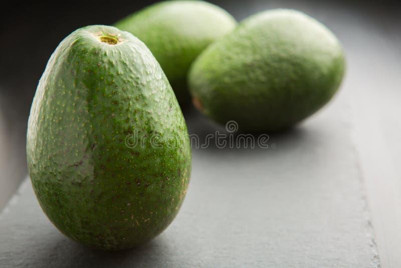 Three raw fresh avocado on black slate plate on dark background. Three raw fresh avocados on black slate plate on dark background. Selective focus stock photos