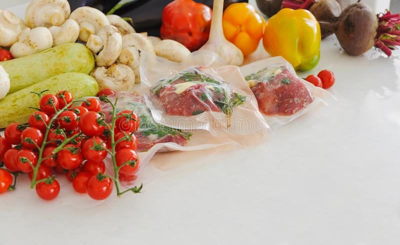 Three raw steaks in vacuum package, vegetables and mushroom. Sous-vide, new technology cuisine. Horizontal stock photos