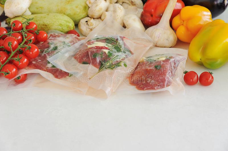 Three raw steaks in vacuum package, vegetables and mushroom. Sous-vide, new technology cuisine. Horizontal royalty free stock image