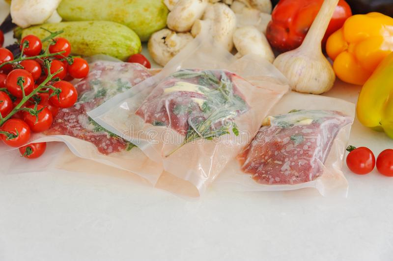Three raw steaks in vacuum package, vegetables and mushroom. Sous-vide, new technology cuisine. Horizontal royalty free stock photos