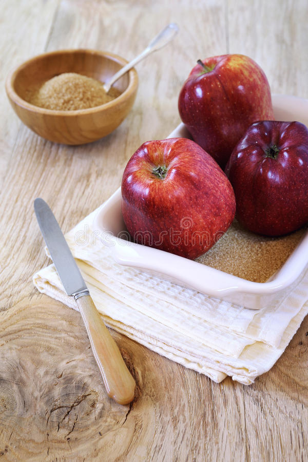 Three red apple in baking dish and brown sugar. Three red apple variety Gala in baking dish, brown sugar and knife stock photos