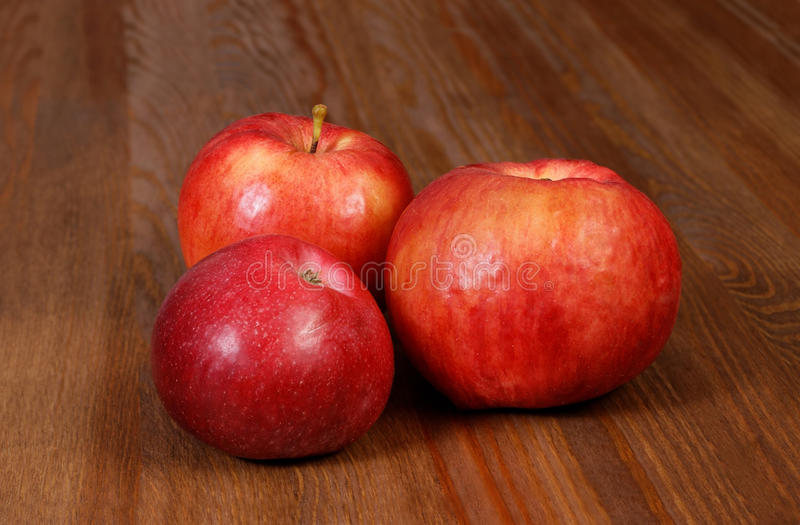 Three Red Apple. On Brown Wooden Table royalty free stock photos