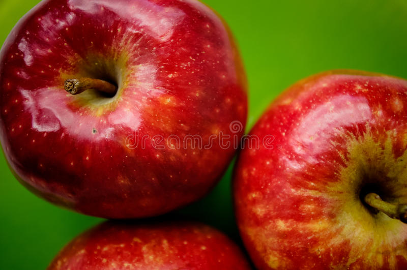 Three red apple on a green background. Close-up view from top royalty free stock photography