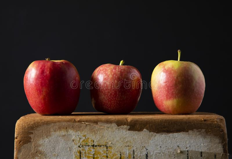 The three red apple on wooden brick in close up, isolated on black background. A three red apple on wooden brick in close up, isolated on black background royalty free stock image