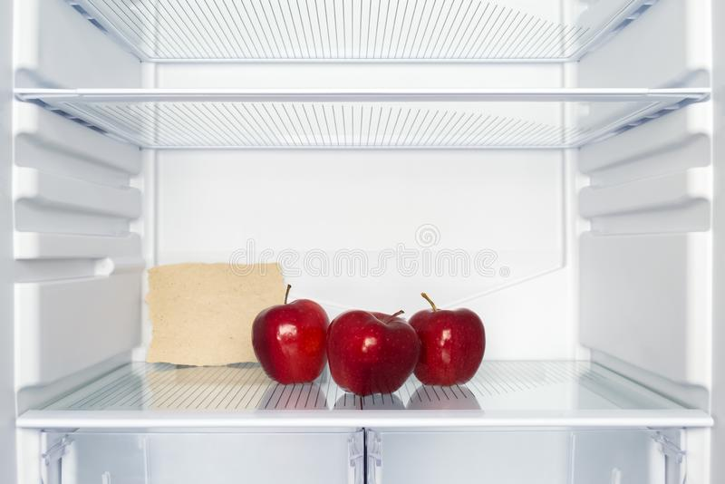 Three red apples in an empty fridge. A sheet of paper with free space for text stock images