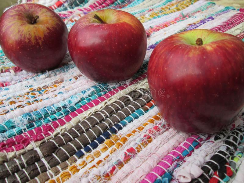 Three Red Apples On A Woven Mat. stock photography