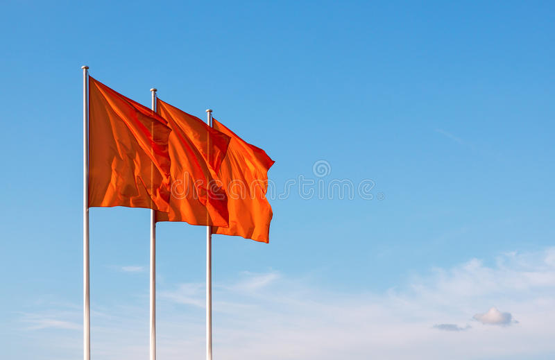 Three red blank flags waving in the wind. Against cloudy sky. Perfect mockup to add any logo, symbol or sign royalty free stock photo