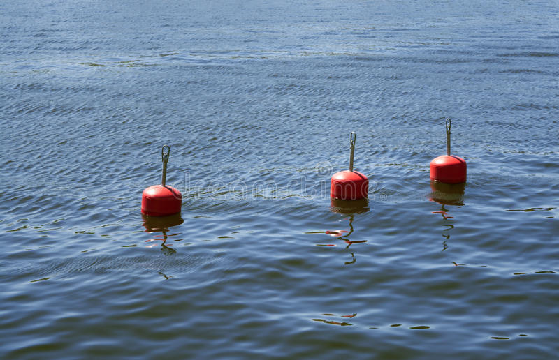 Three red buoys in blue summer sea. Three bright red buoys in a row, floating in shimmering blue summer ocean stock photos