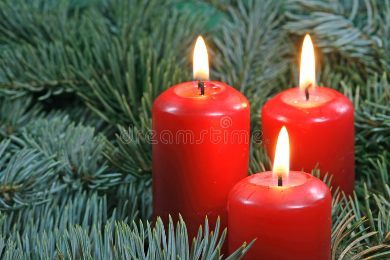Three red candles. And christmas tree bough stock photos