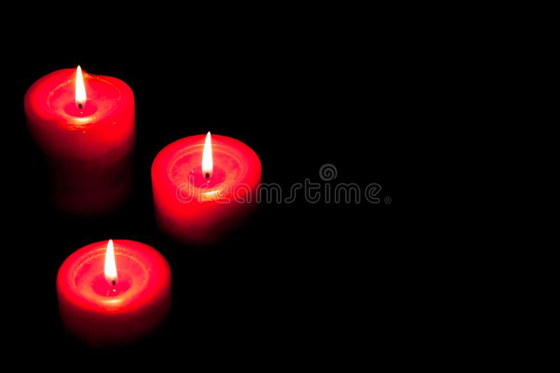 Three red candles on black background stock images