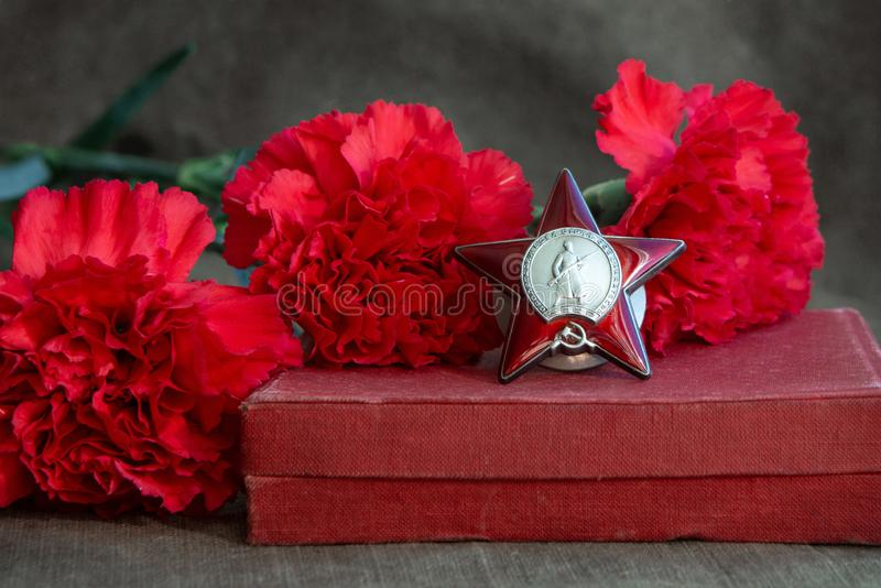 Three red carnations, the Order of the Red Star on the canvas. Symbols of the Great Patriotic War. May 9. Victory Day stock images
