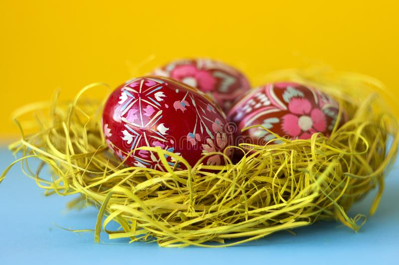 Three red decorated Easter eggs lie in a nest of hay on a yellow and blue background. Ukrainian Easter eggs with ornaments and royalty free stock image