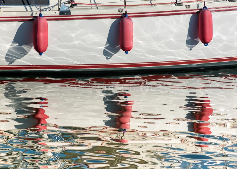 Three red fenders hanging over the hull of a boat. Reflecting in the sparkling sunlit water of the harbor below royalty free stock photos