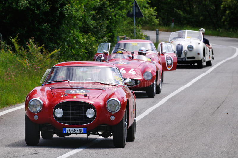 Three red Ferrari and a white Jaguar classic cars royalty free stock photo