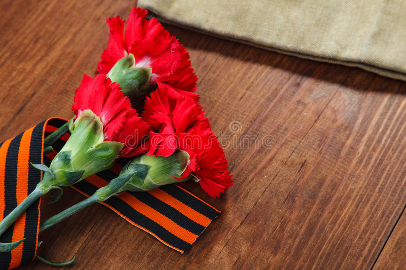 Three red flower and paper and Soldier's forage cap on a wooden background. selective focus image royalty free stock photo
