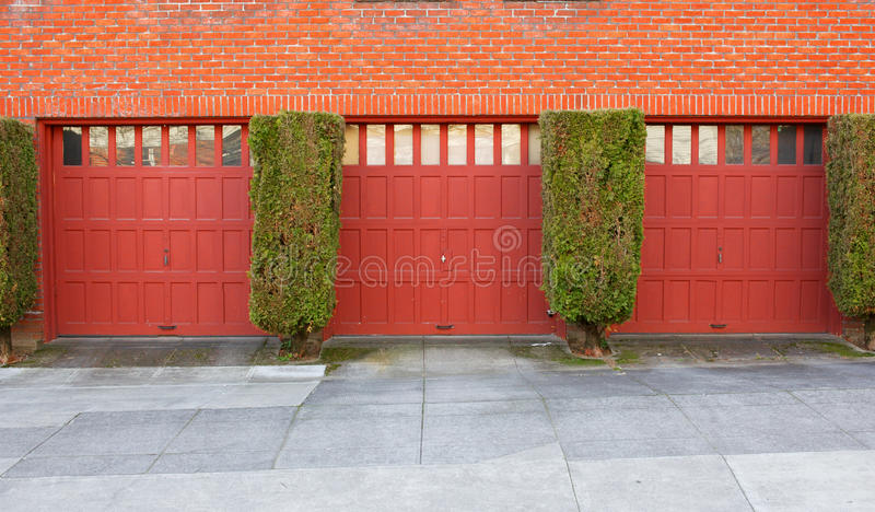 Three Red Garages. On a brick wall separaged by evergreen bushes royalty free stock photo