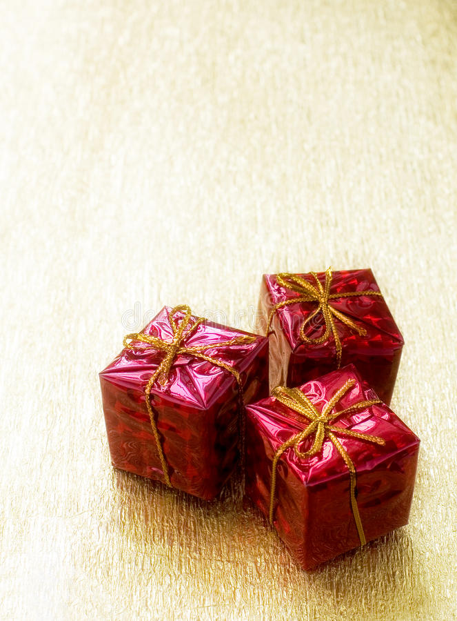 Three red gift boxes on a golden background stock photo
