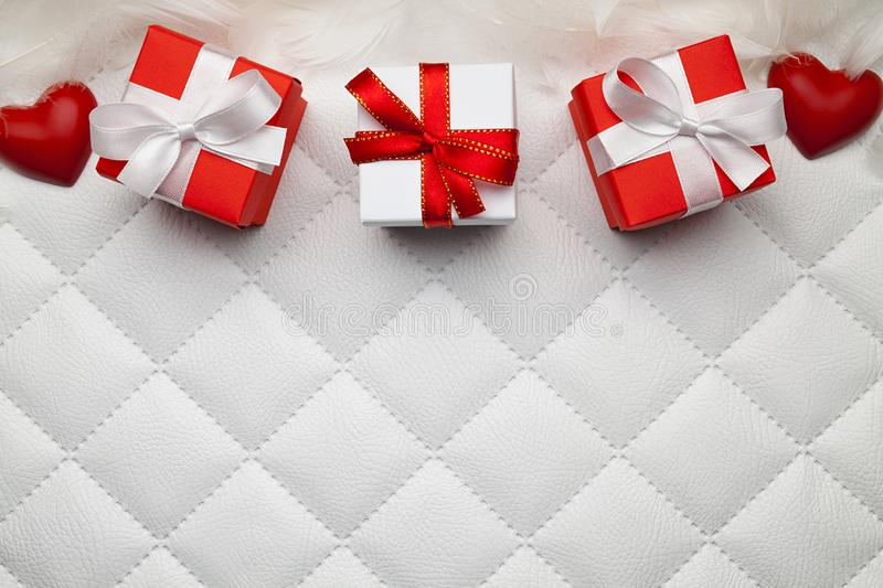 Three red gift boxes and red hearts on white leather background royalty free stock photo