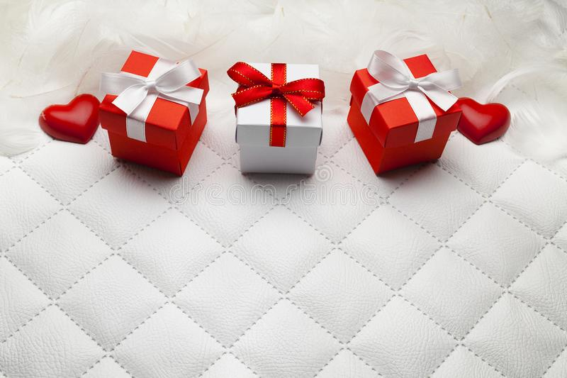 Three red gift boxes and red hearts on leather background stock photography