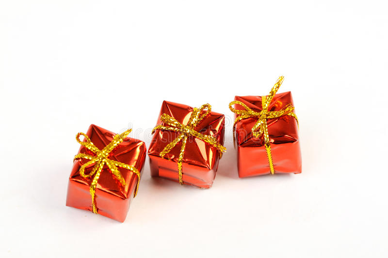 Three red glossy gift boxes with gold bow in the line on white background royalty free stock images