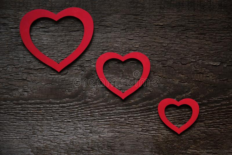 Three red hearts arranged diagonally on an old wooden brown Valentine`s Day board royalty free stock photos