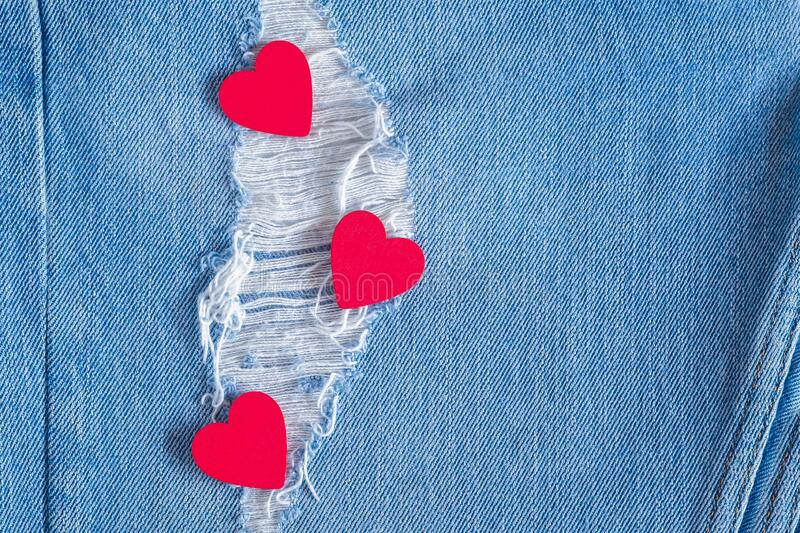 Three red hearts on old denim background. Concept Valentine`s Day stock image